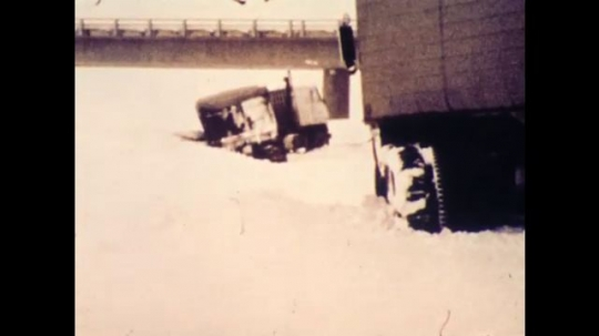United States: 1970s: lorry stuck in snow. Cows in snow. Homes covered in snow. Boys watch television.