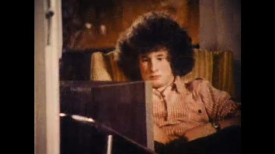 United States: 1970s: teenage boy watches television from chair. View of young man from outside of house.