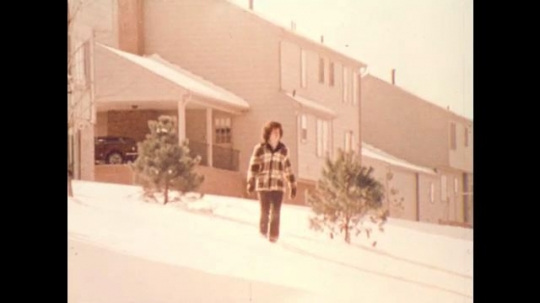 United States: 1970s: boy walks through snow in street. Boy feels cold in snow.