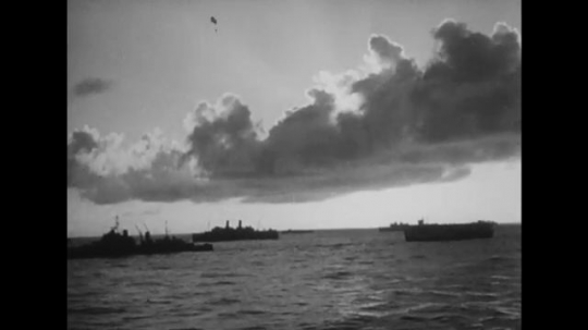UNITED STATES: 1940s: clouds above ships at sea. Sailors and military men on ship. Soldiers smile and wave at camera from deck of ship. Guns.