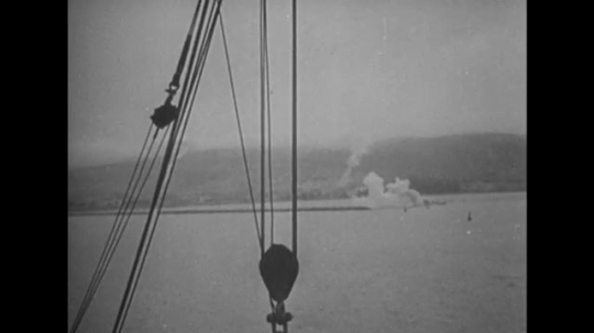 UNITED STATES: 1940s: view of gunfire through ropes on boat. Boats land. Soldiers on boats.