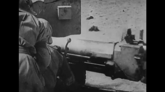 UNITED STATES: 1940s: soldiers fire guns in desert. Tank hit by weapons.