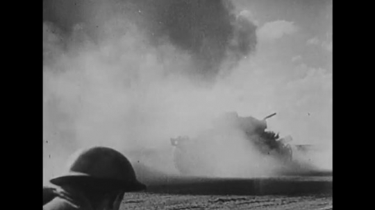 UNITED STATES: 1940s: air strikes by tanks in sand. Soldiers run through dust. Body dangles from tank.