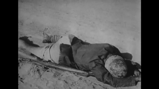 UNITED STATES: 1940s: dead soldiers on ground. Soldiers walk across desert.