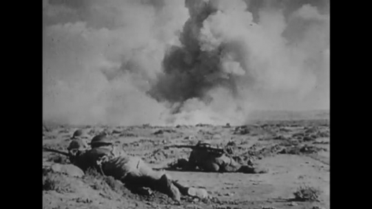 UNITED STATES: 1940s: soldiers fire weapons. Explosions in sand. Tanks in battle. Soldiers run through dust cloud.