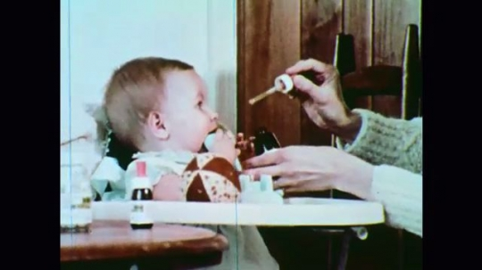 United States: 1970s: lady gives medicine to baby. Man fills kettle with fuel. Lady makes tea. Family prepare supplies. Man puts batteries in torch. Train on tracks. Lorry reverses