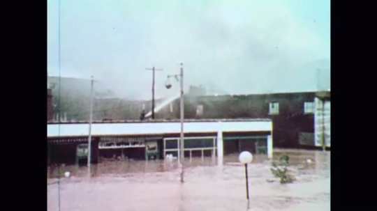 United States: 1970s: buildings catch fire in flood. Man sprays hose on building. Black smoke above flooded buildings