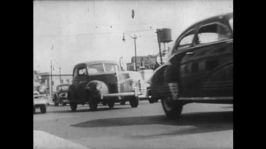 UNITED STATES: 1950s: Cars on busy street. Traffic on road. Farmer drives truck. Bus and truck on road.
