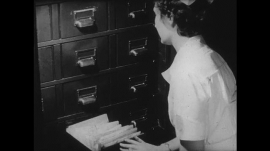 UNITED STATES: 1950s: nurse locks papers in cupboard. Motor vehicle permit. Cars on street