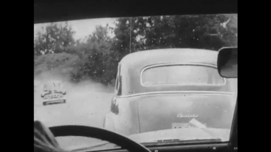 UNITED STATES: 1950s: car drives along road. People at desk.