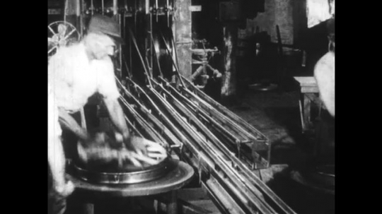 UNITED STATES: 1950s: gravity slides move components to workers. Conveyor belt in factory.