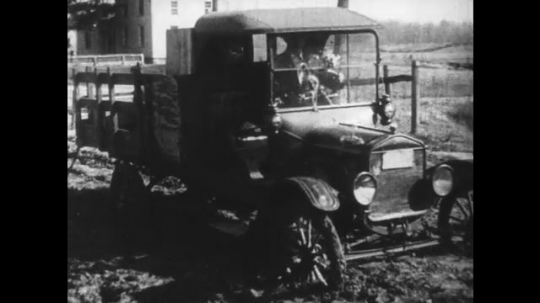 UNITED STATES: 1950s: vehicle gets stuck on muddy road. Workers make roads.