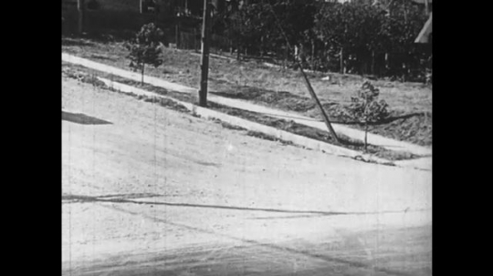 UNITED STATES: 1950s: car rolls down hill. Man catches car. Man switches road sign