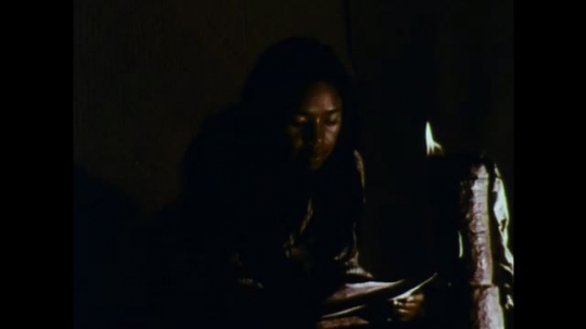 MADAGASCAR: 1970s: Lady reads letter by candle light. Close up of lady