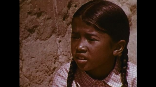 MADAGASCAR: 1970s: girl watches lady weaving. Chicken by girl. Man arrives