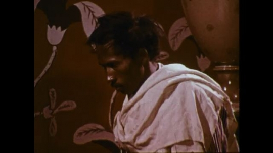 MADAGASCAR: 1970s: man stands in robe. Men stand by wall.