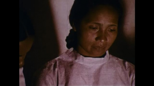MADAGASCAR: 1970s: man and woman prey with family in room. Men look through window.