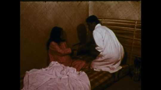 MADAGASCAR: 1970s: man comes to room and takes man away. Pregnant lady sits on bed. Ladies in street