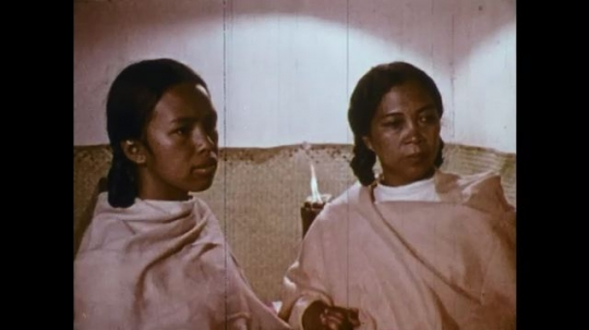 MADAGASCAR: 1970s: Man talks to woman and girl. Lady walks through town. Candle burns.