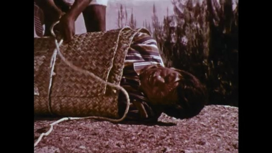 MADAGASCAR: 1970s: men tie man in mat on edge of cliff. Girl looks up to sky and clouds.