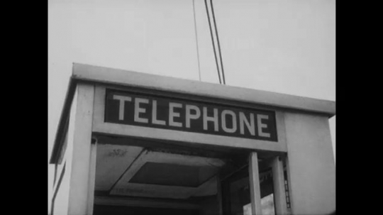 UNITED STATES: 1960s: Telephone box. Man makes call from box. Police speak on phone. Building on fire