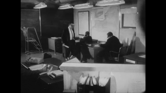 UNITED STATES: 1960s: men work as team in office. Emergency Operations team. Man makes call