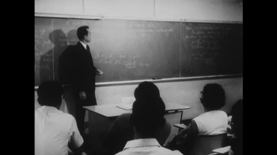 UNITED STATES: 1960s: Man presents to class from blackboard. Police officer in car at night