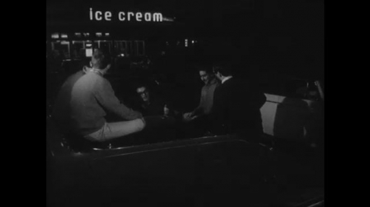UNITED STATES: 1960s: people at ice cream parlour on street. Police man speaks to young people on street. Teens look at watches