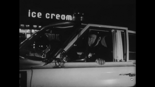UNITED STATES: 1960s: police man n car outside ice cream parlour. Police car drives along road