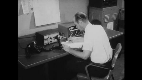 UNITED STATES: 1960s: man makes notes by communications equipment. Lady approaches man at desk. Siren system.