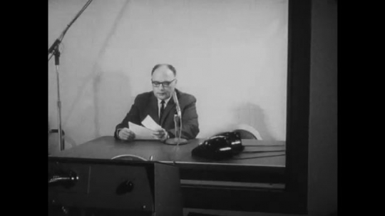 UNITED STATES: 1960s: man speaks to microphone over emergency broadcast system. Man reds check list. People sit at home.