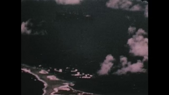PACIFIC OCEAN: 1940s: ships arrive at island. Nuclear explosion by island. Clouds over atoll.