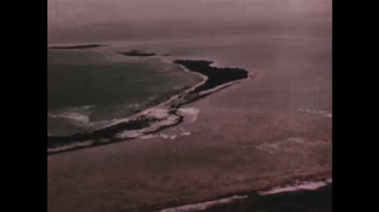 PACIFIC OCEAN: 1940s: waves break on coral reef. Animation of radioactivity. View across lagoon. Coral reef in ocean
