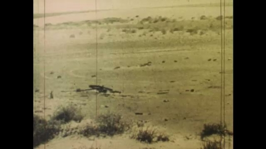 UNITED STATES: 1980s: view across bare land. Vehicles on land. Cracked mud. Fence across land