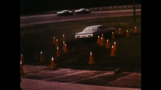 UNITED STATES: 1970s: car reverses into area marked by cones. View through car windscreen. Man at wheel of car.