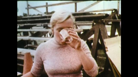 UNITED STATES: 1970s: man drinks cup of alcoholic beverage. Drivers stand in group. People arrive at stadium.