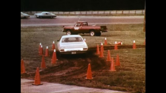 UNITED STATES: 1970s: car reverses through cones. Car drives on track