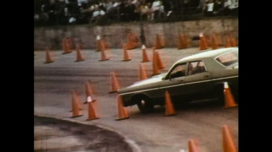UNITED STATES: 1970s: car reverses through cones. People in crowd watch cars on track.