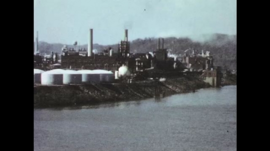 UNITED STATES: 1950s: factory buildings and chimneys by waterway. Buildings at night. Train cars make contact. Animated map.
