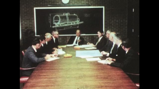 UNITED STATES: 1950s: men at table in meeting. Man on telephone in office
