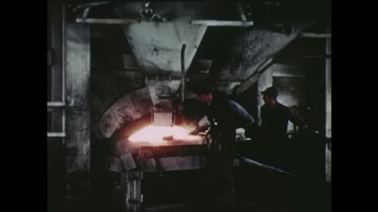 UNITED STATES: 1950s: men stoke glass furnace in factory.