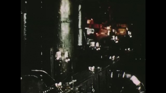UNITED STATES: 1950s: glass container factory. Machine cuts molten glass. Glass blowing