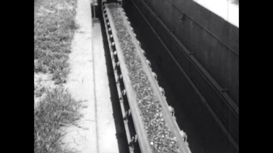 1950s: United States: iron ore on conveyor belt. Coke in railroad cars.