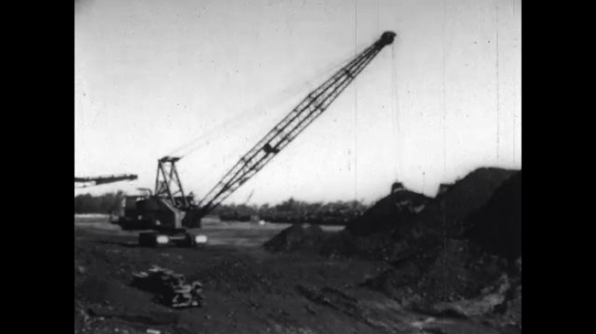 1950s: United States: stock pile on coal. Machine moves coal from pile to hopper.