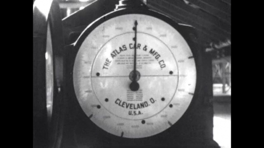 1950s: United States: close up of scale for weighing railroad cars. Operators analyze weight and quality of materials