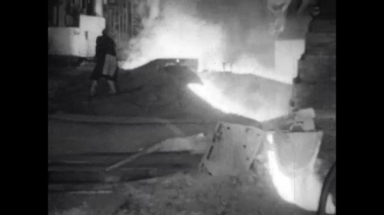 1950s: United States: molten iron and slag removed from pile by worker.