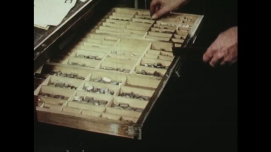UNITED STATES: 1950s: hand prepares printing press letters and blocks.