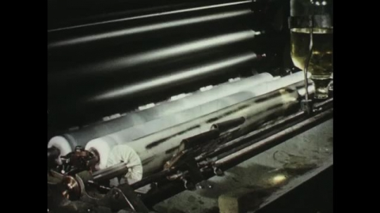UNITED STATES: 1950s: rollers on printing press. Machine components on printing press. Sheets of paper in press.