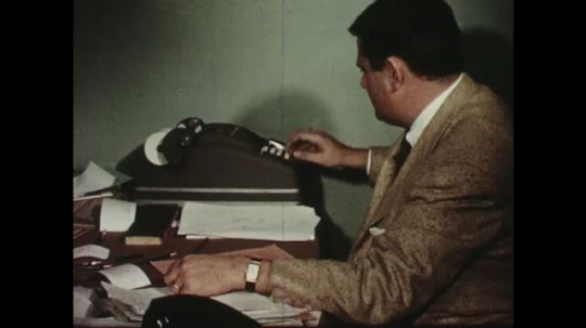 UNITED STATES: 1950s: man types numbers into machine and print receipt. Man writes notes in book