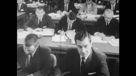 UNITED STATES: 1960S: men sit at desks for talk. Man points at graph on board. Building for fallout protection class. People arrive at shop. Men inspect building.